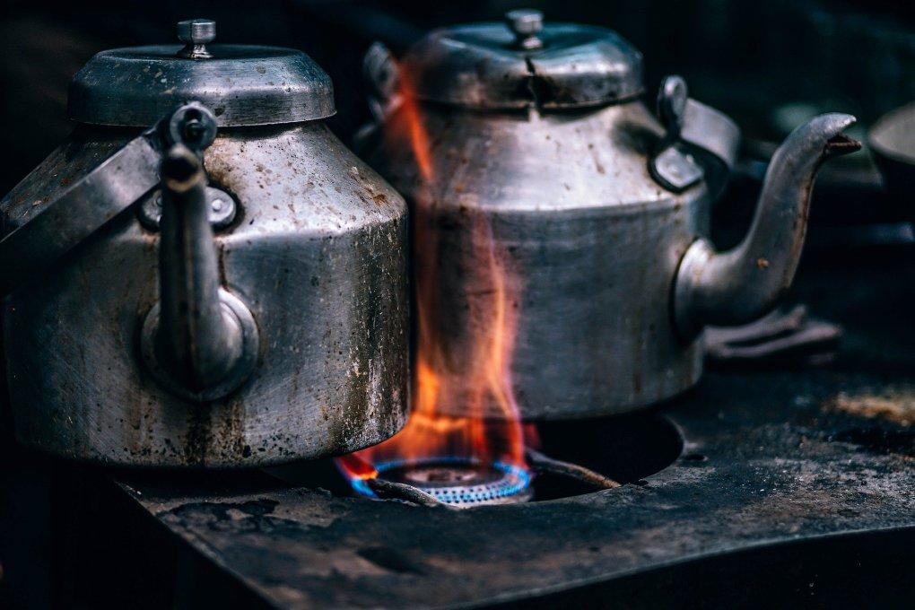 Imagem mostra duas chaleiras de ferro no forno.