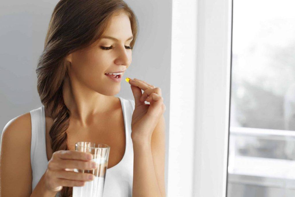 Mulher tomando cápsula.