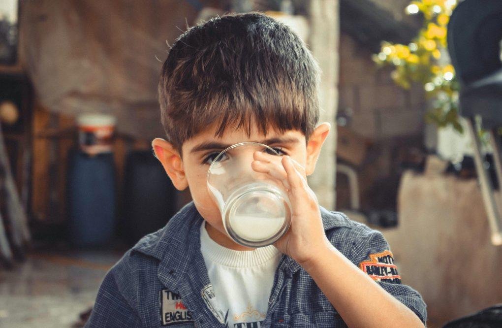 Imagem mostra uma criança tomando um copo de leite.