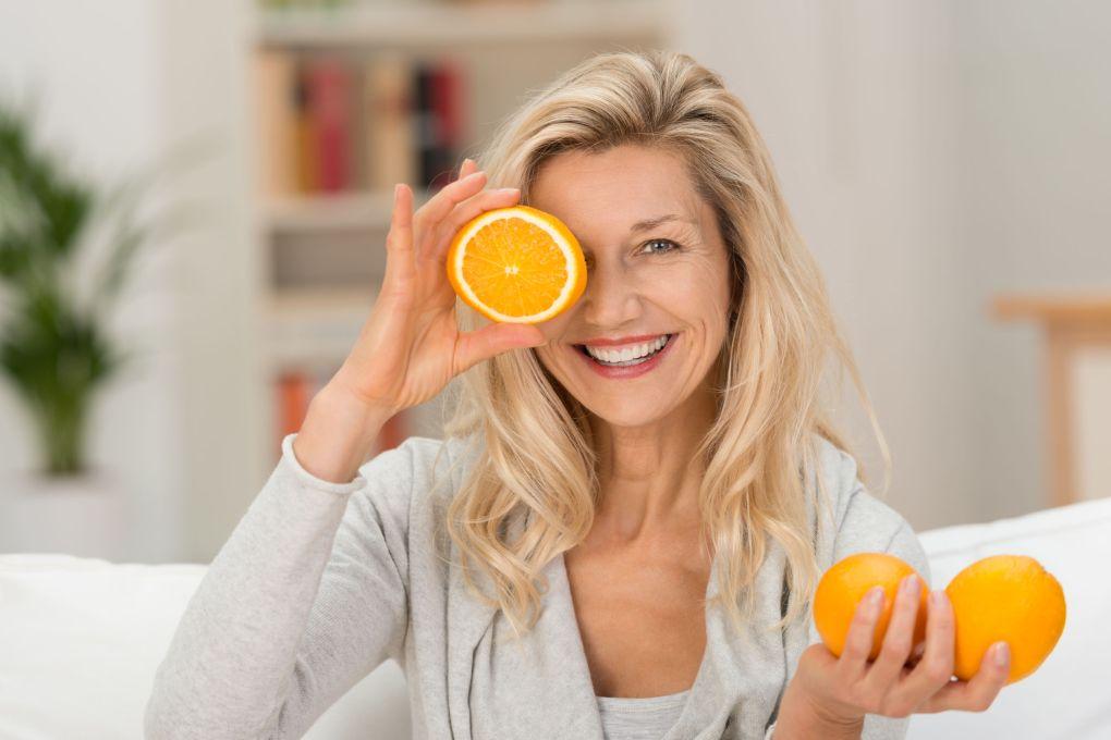 Felice donna in buona salute che gioca con arance fresche mature che tengono due in mano e un terzo frutto dimezzato al suo occhio con un bel sorriso