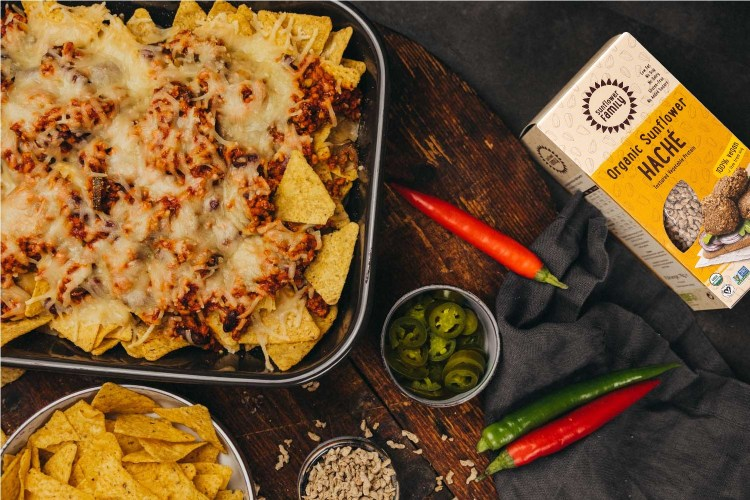 Plate of nachos with box of sunflower hache, bowl of jalapenos, and peppers.