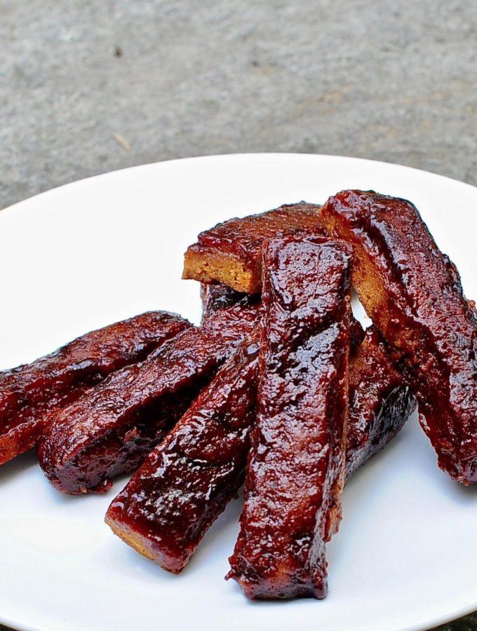 a pile of seitan ribs on a white plate.