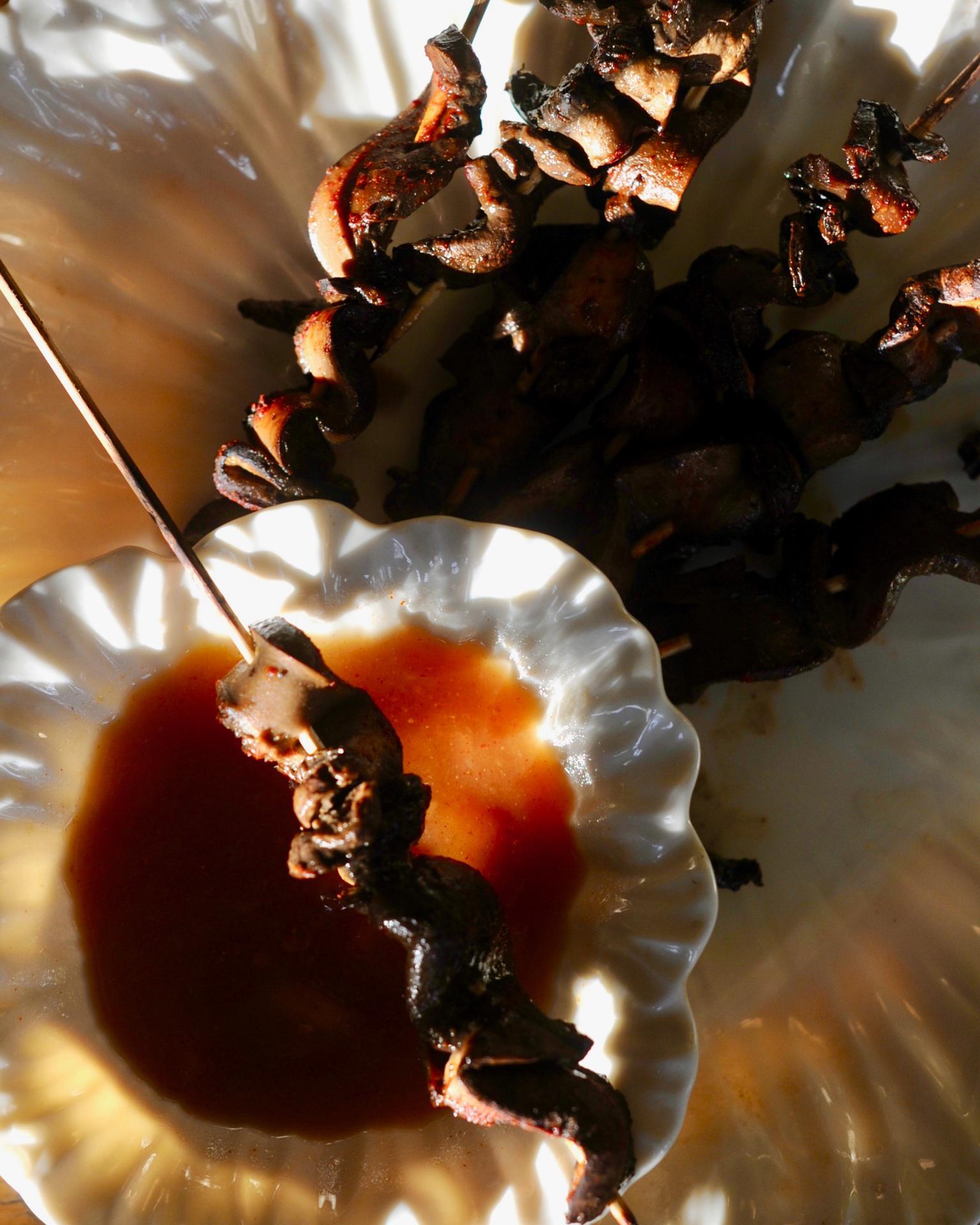 Mushroom satay skewer resting on mango dipping sauce in white bowl