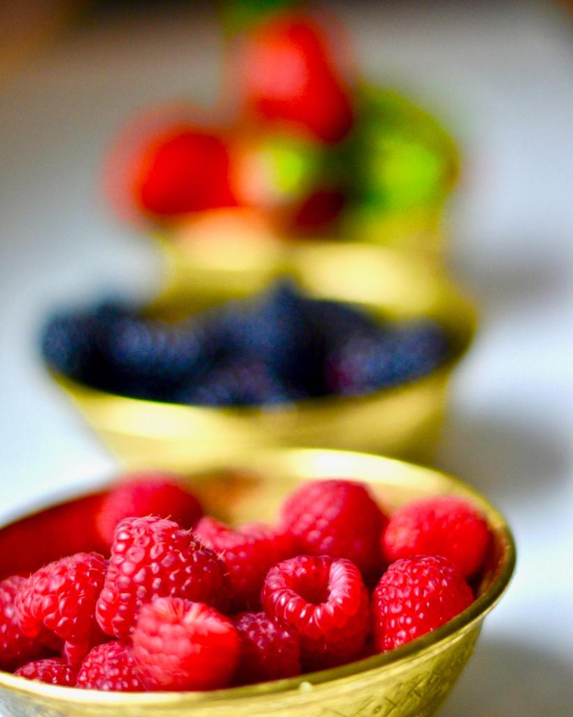 Gold bowls with fresh blackberries, raspberries and strawberries