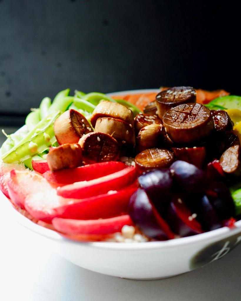 Sliced plums and mushrooms in a white vegan Vegan Scallop Poké Bowl with Sesame Lime Sauce