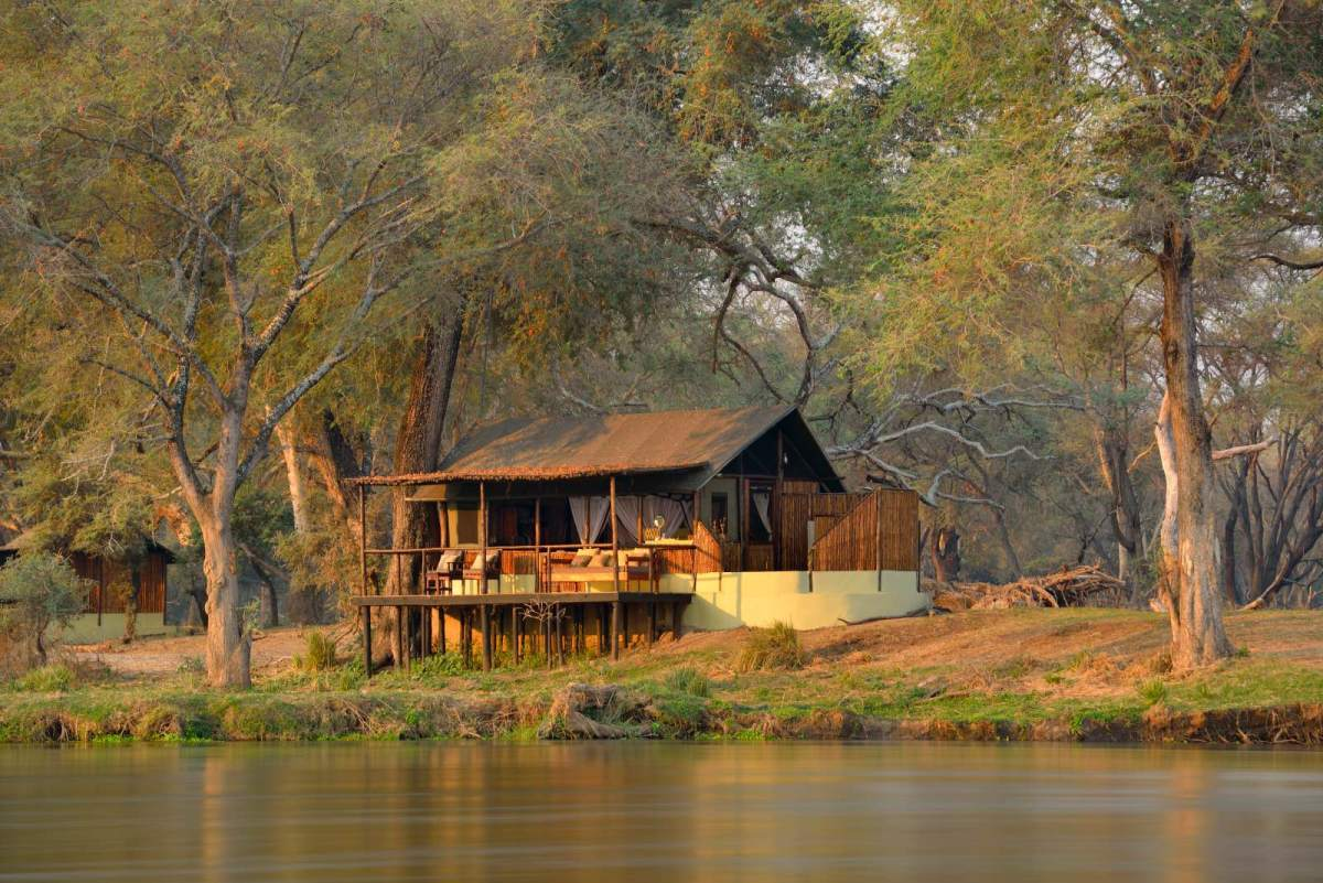 Rustic thatched chalets on the banks of the river at Old Mondoro