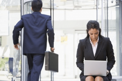 Revolving door business woman and man leaving