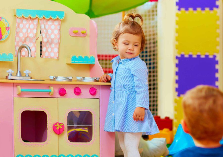 Bambina davanti a una cucina giocattolo