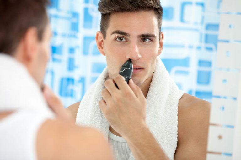 Uomo davanti allo specchio con il tagliapeli per il naso