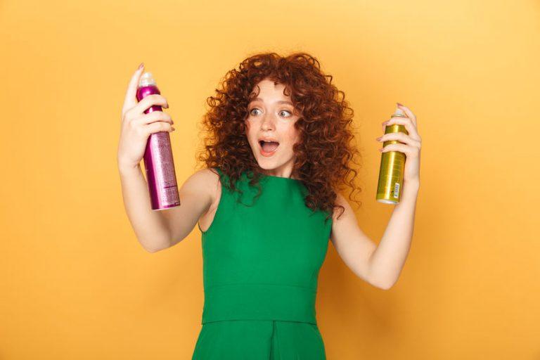 Redhead dai capelli ricci con due spray shampoo a secco su sfondo arancione