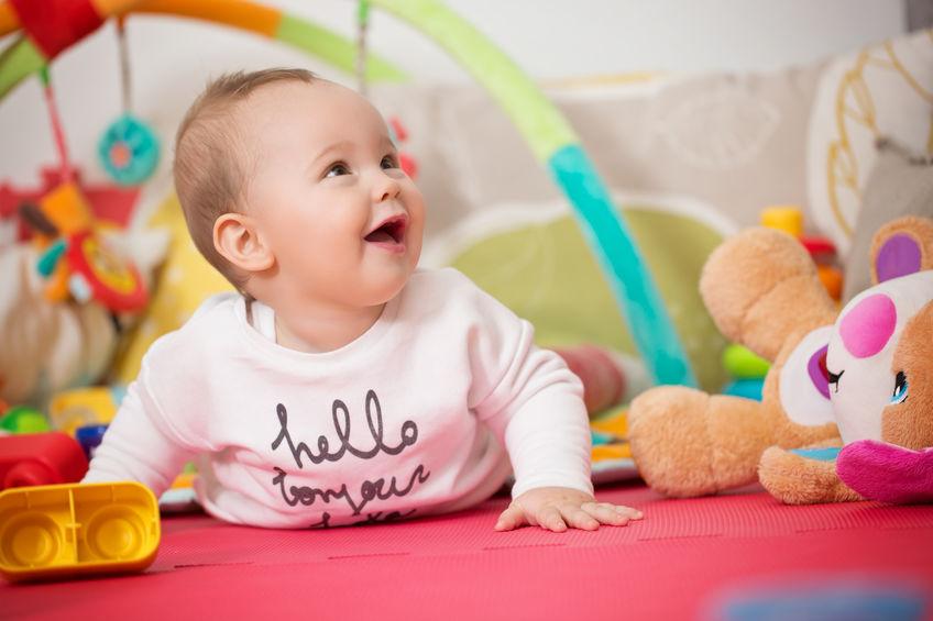 Bambina di otto mesi che gioca con i giocattoli colorati su un pavimento