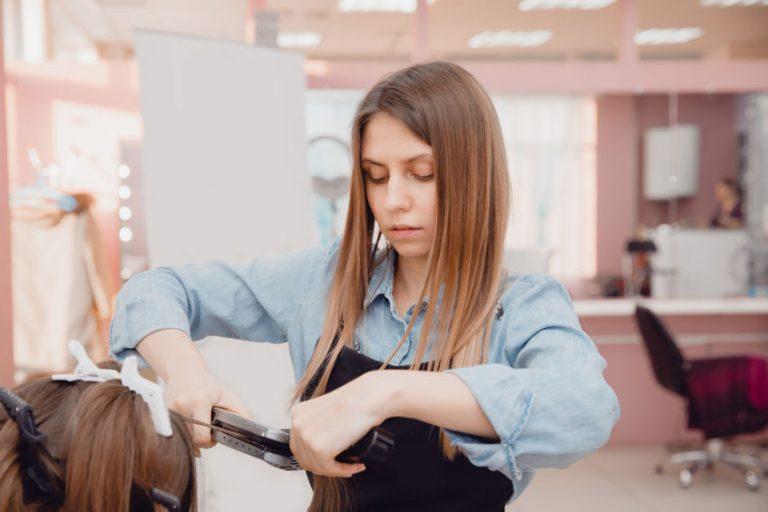 Parrucchiera che usa una piastra per capelli professionale