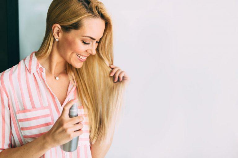 Donna dai capelli chiari che applica shampoo a secco