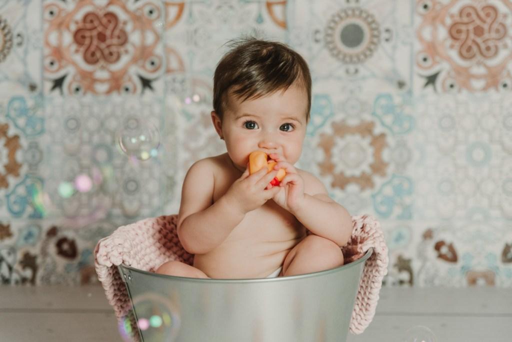 bebe en cubo con pompas de jabon