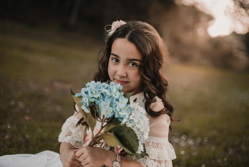 retrato de niña de comunión con flores en la mano