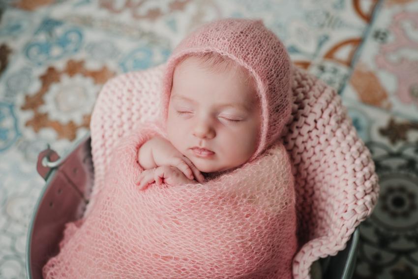 fotgrafia de recien nacido en cubito con gorro rosa