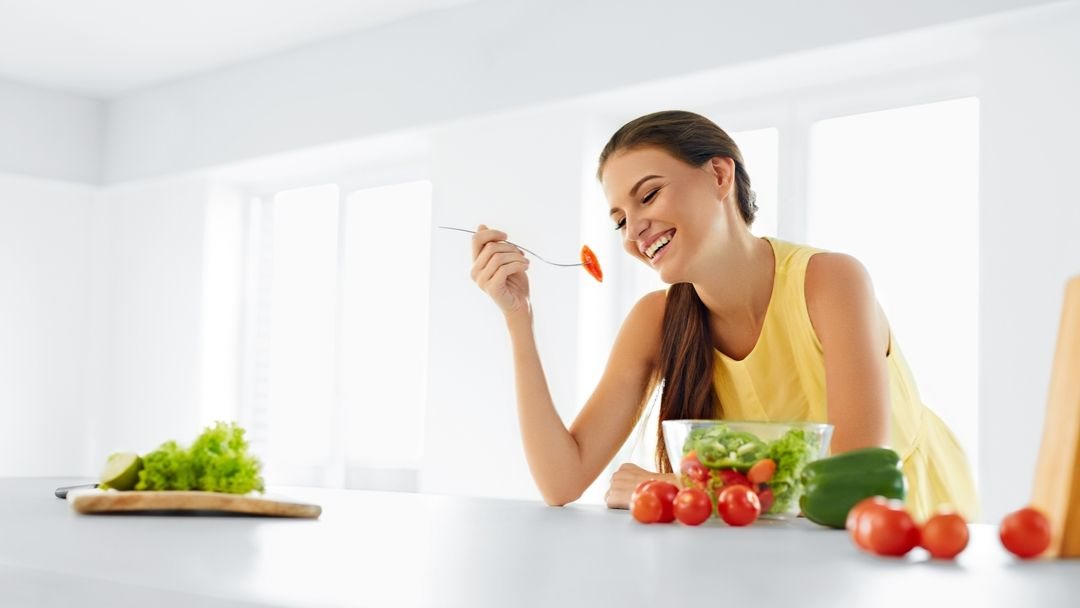 Women at counter eating a healthy salad