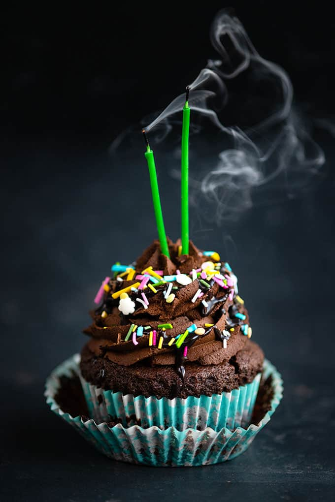 Chocolate cupcake with chocolate frosting and sprinkles with 2 candles