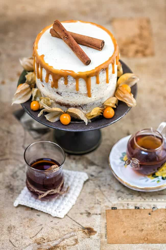 A spectacular layered carrot cake recipe with chai infused raisins, rich mascarpone frosting and addictive chai tea caramel.