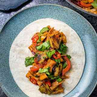 You won't believe these tacos are vegan! Jackfruit replaces pulled pork seamlessly in these spicy tacos served with grilled pineapple.