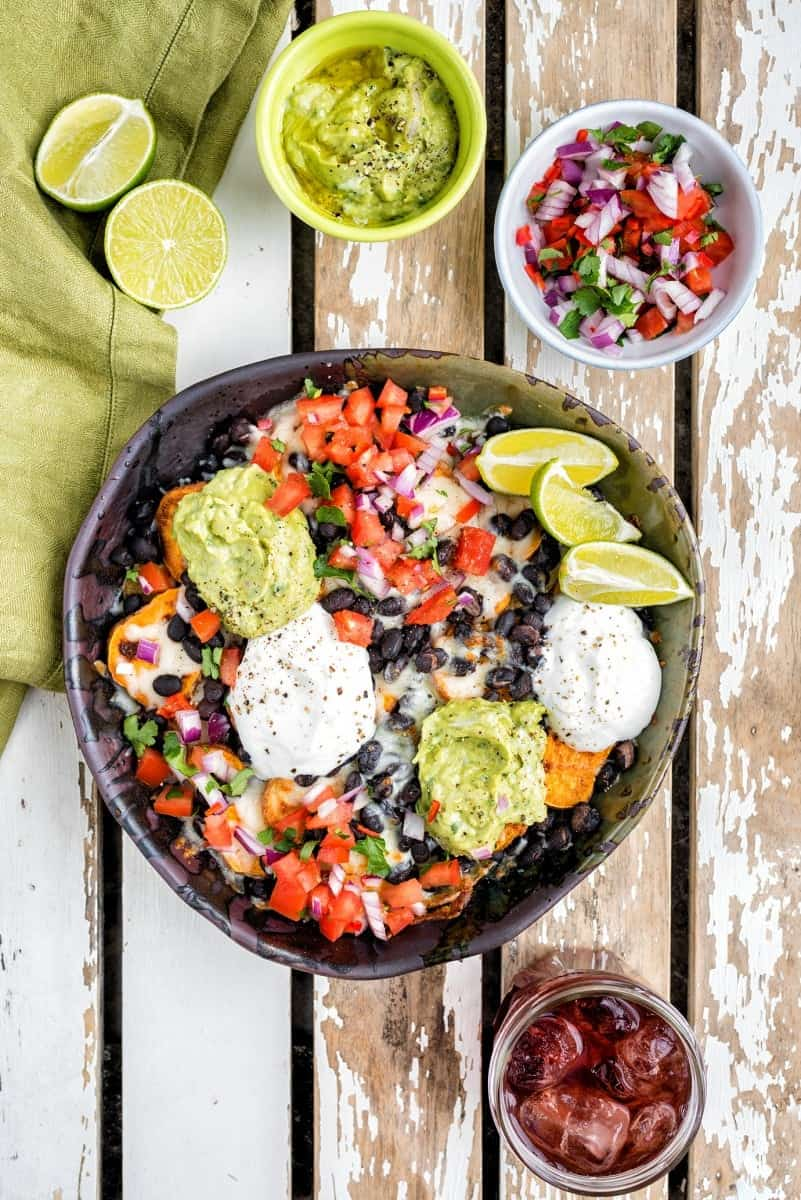 Fully loaded vegetarian sweet potato nachos with guacamole and salsa