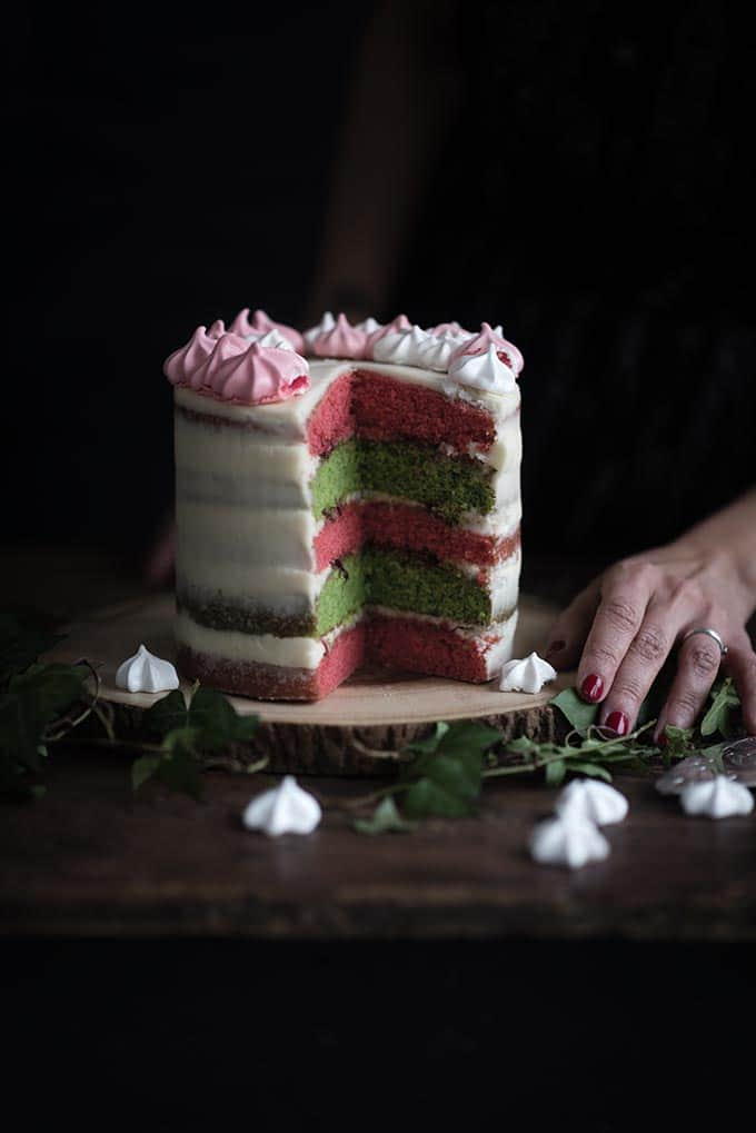 Showstopping Christmas layer cake with green and red layers and a meringue wreath crown
