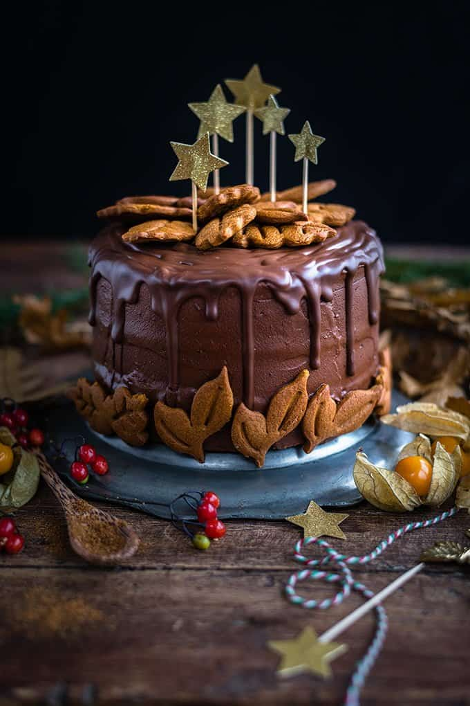 Incredibly delicious vegan chocolate gingerbread layer cake decorated with gingerbread cookies