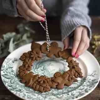 Vegan gingerbread cookies are easy, delicious and perfect for turning into a festive mini gingerbread cookie wreath! These adorable wreaths make great cake decorations or table settings... possibly too cute to eat!