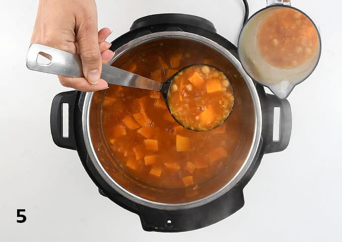 Transferring a ladleful of vegan soup to a jug for blending