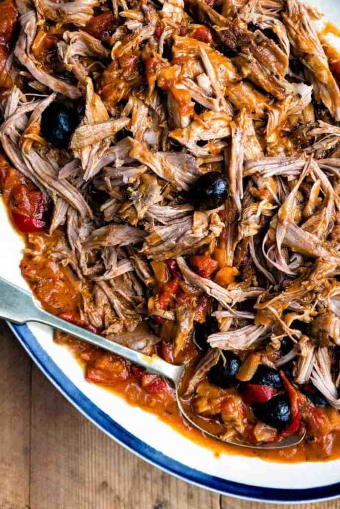 Close up on a platter of pulled lamb in rich tomato sauce with black olives