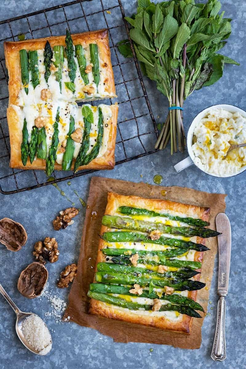 Two puff pastry tarts topped with asparagus