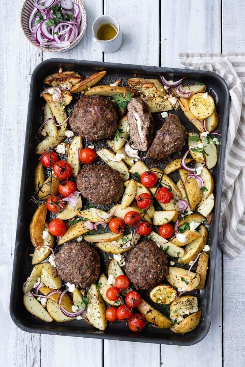 Oven tray with Greek bifteki, potato wedges and vine tomatoes
