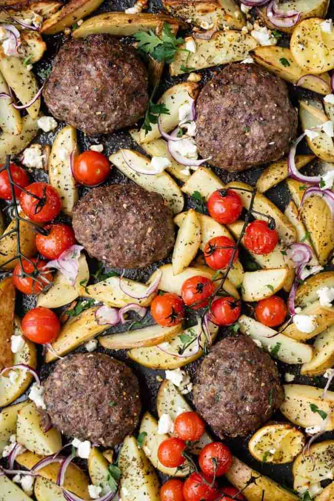 Close up of Greek bifteki with potato wedges and tomatoes