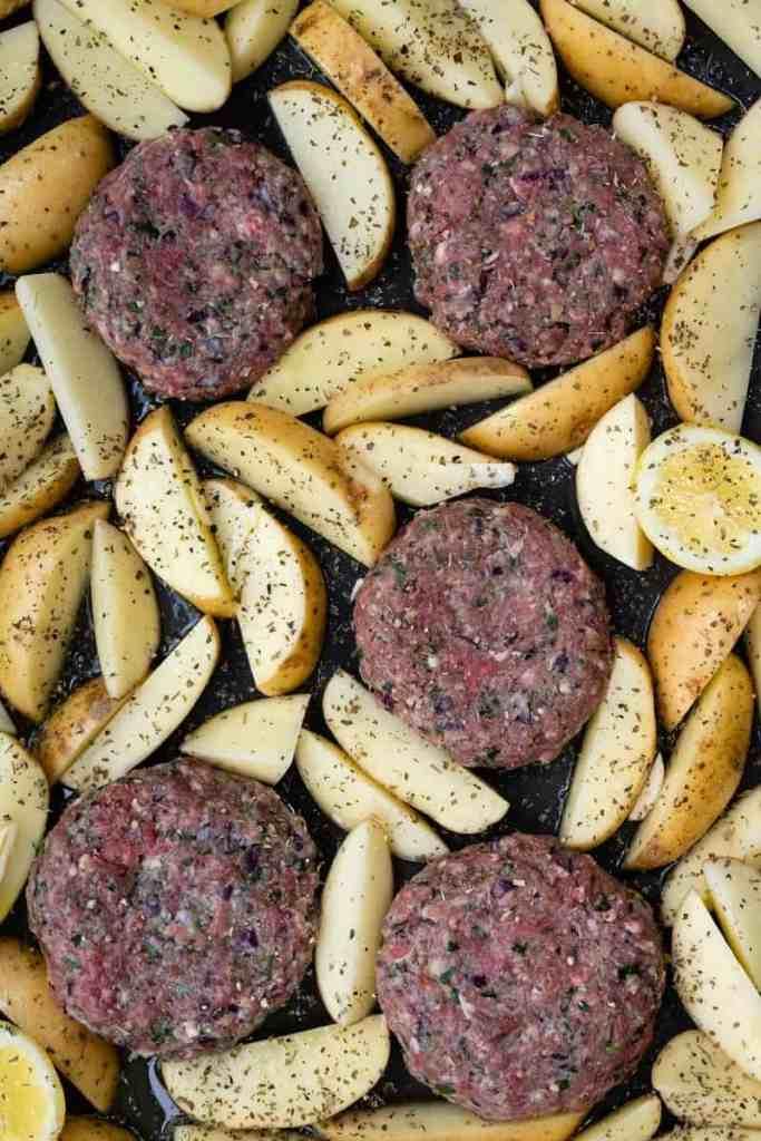 Greek bifteki and potato wedges in a sheet pan