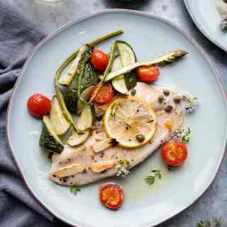 Oven-baked tilapia with vegetables on a plate
