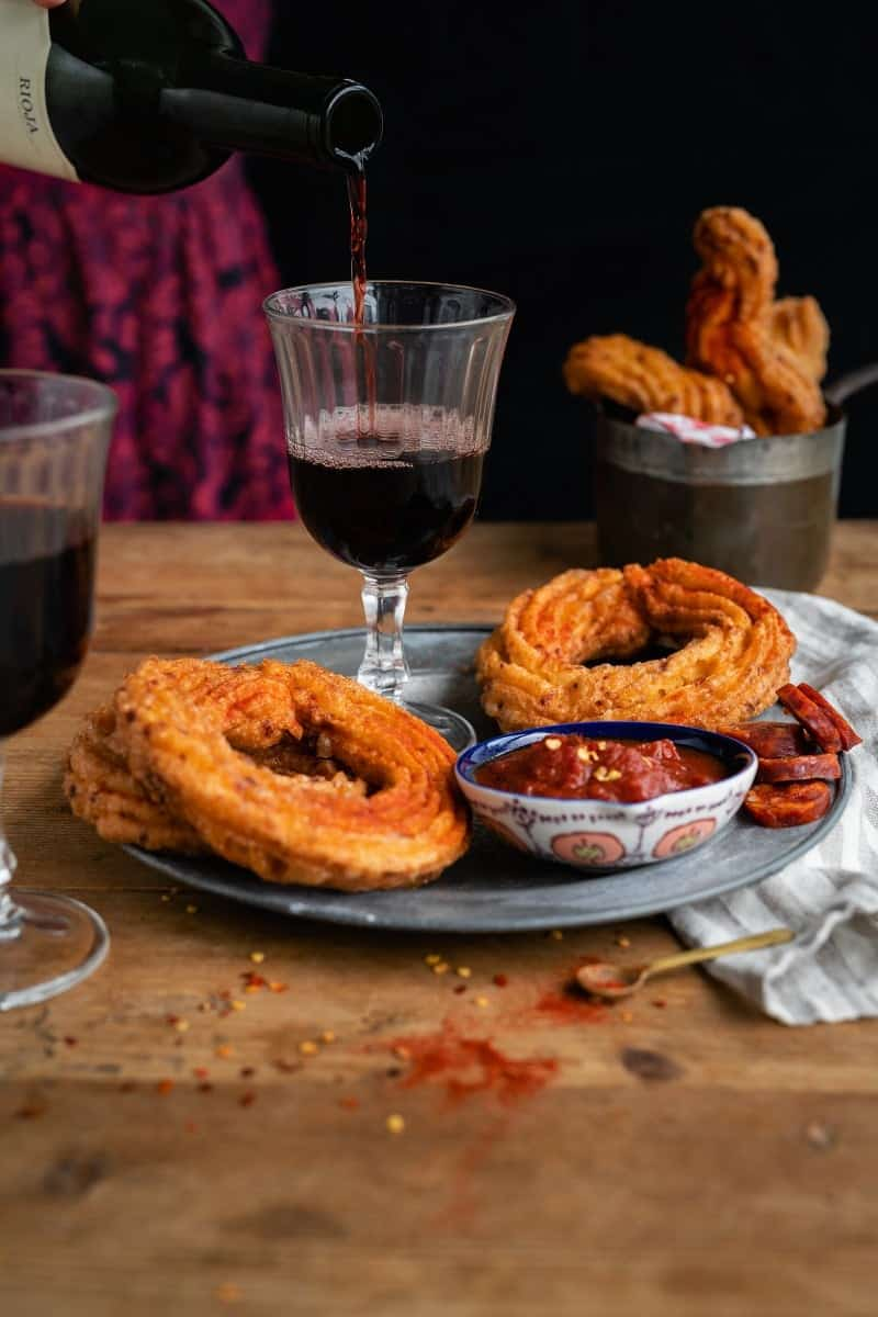 Savoury churros served with tomato dipping sauce and a glass of Rioja