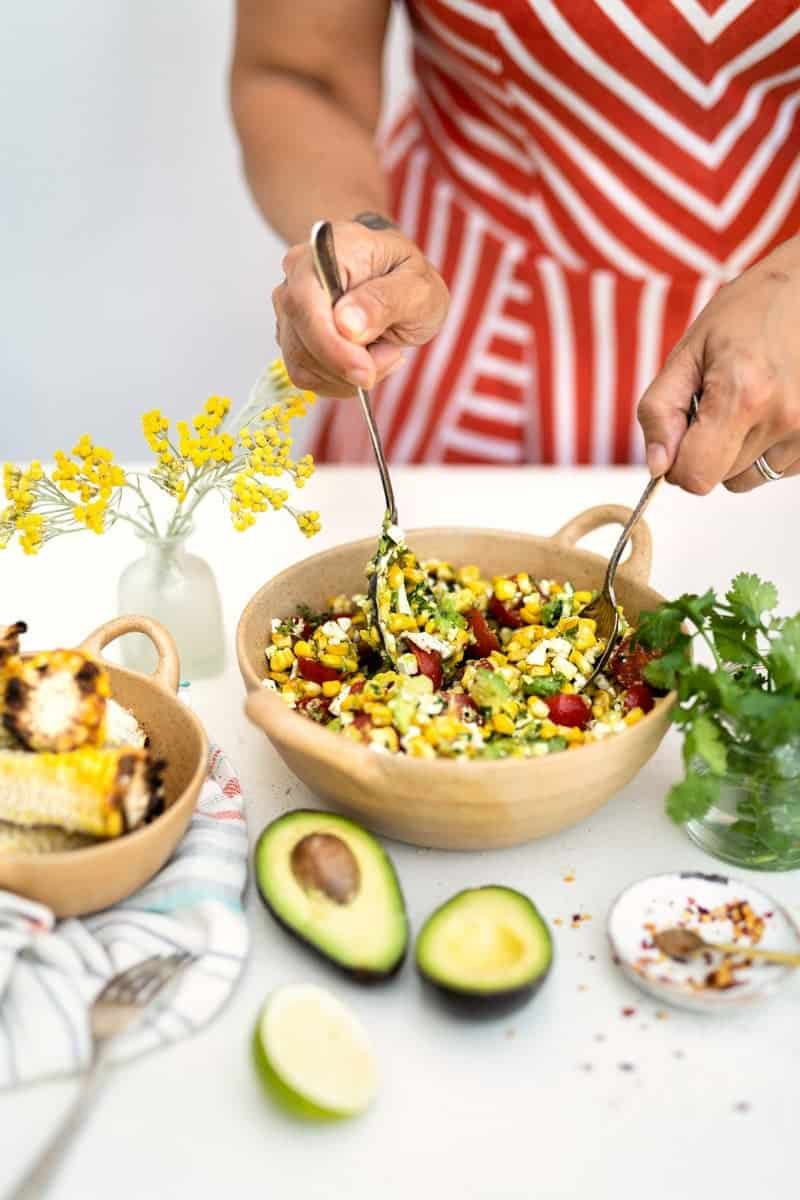 Mixing grilled corn, feta and avocado salad in a bowl