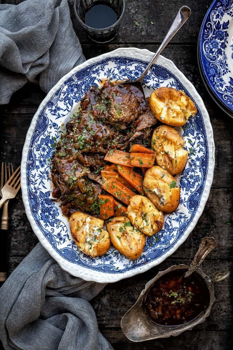 Sliced balsamic beef brisket arranged on a blue platter with potatoes and carrots