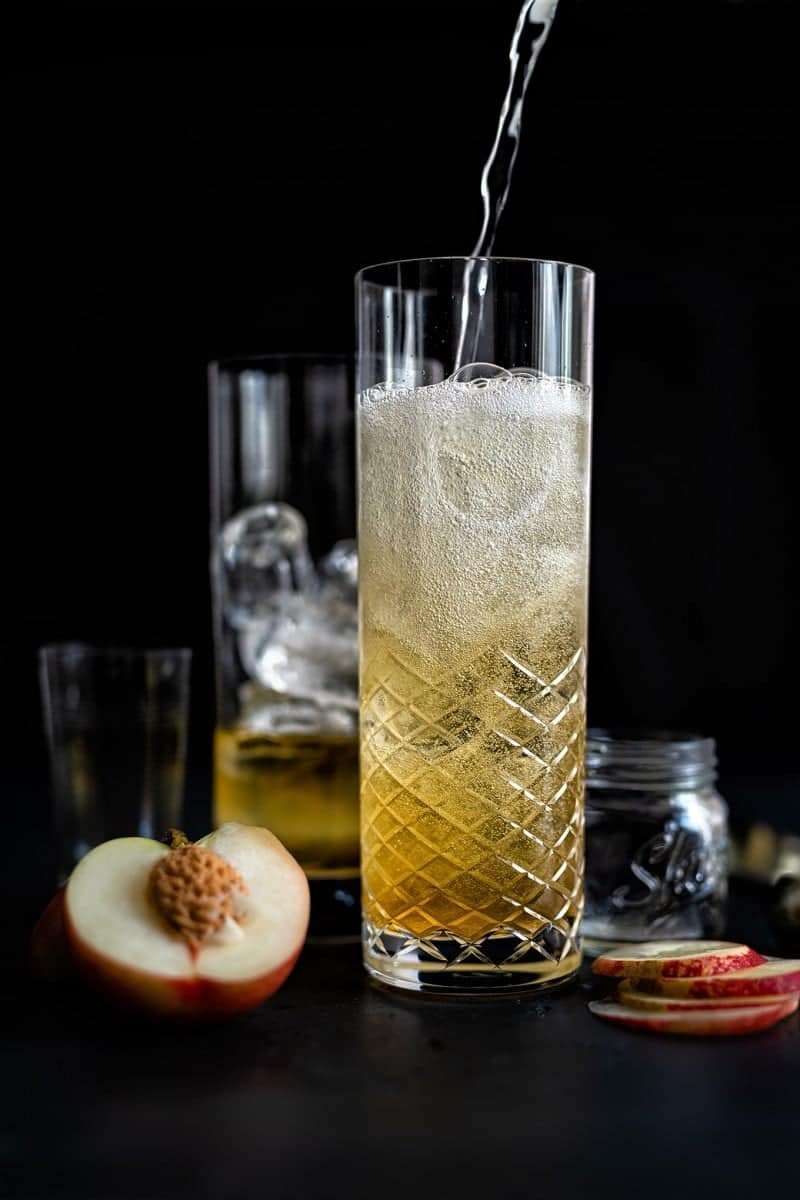 Topping a sparkling peach whisky cocktail with chilled soda water