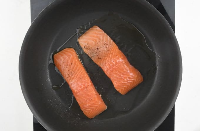 Searing salmon fillets in a pan