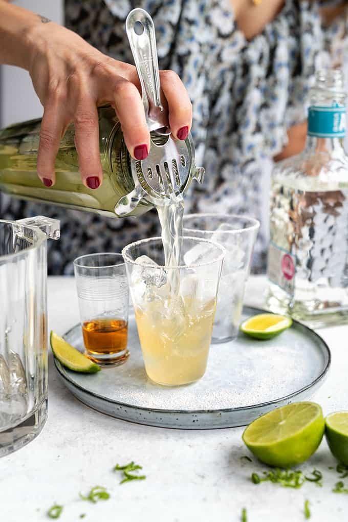 Cadillac Margarita being strained into a glass filled with ice with Grand Marnier on the side
