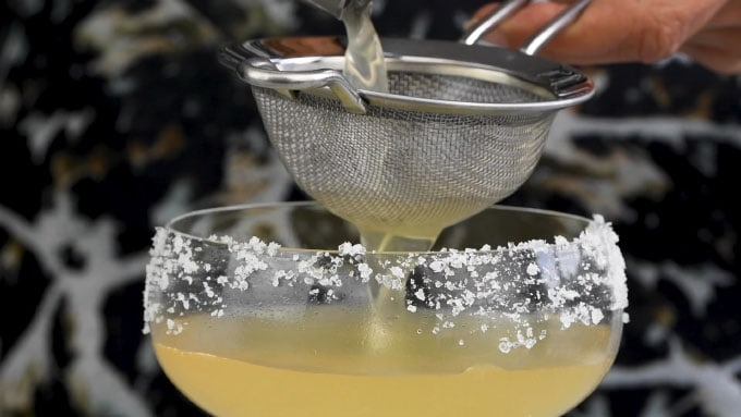Close up of double straining a Grand Margarita into a frosted coupe glass