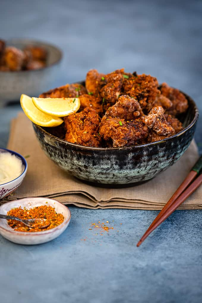 Bowl of Japanese Fried Chicken with lemon wedges and mayonnaise on the side