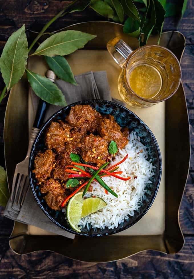 Indian Bhuna Gosht curry in a bowl with rice garnished with sliced chillies