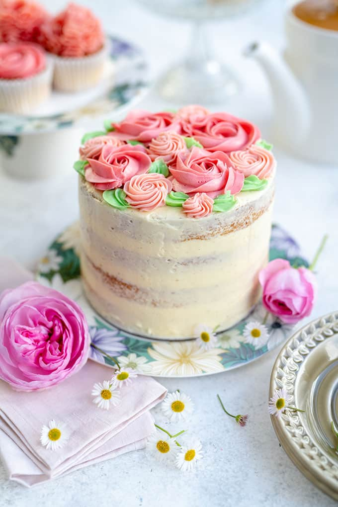 Birthday Cake Decorated With Pink Buttercream Roses On A Floral Plate