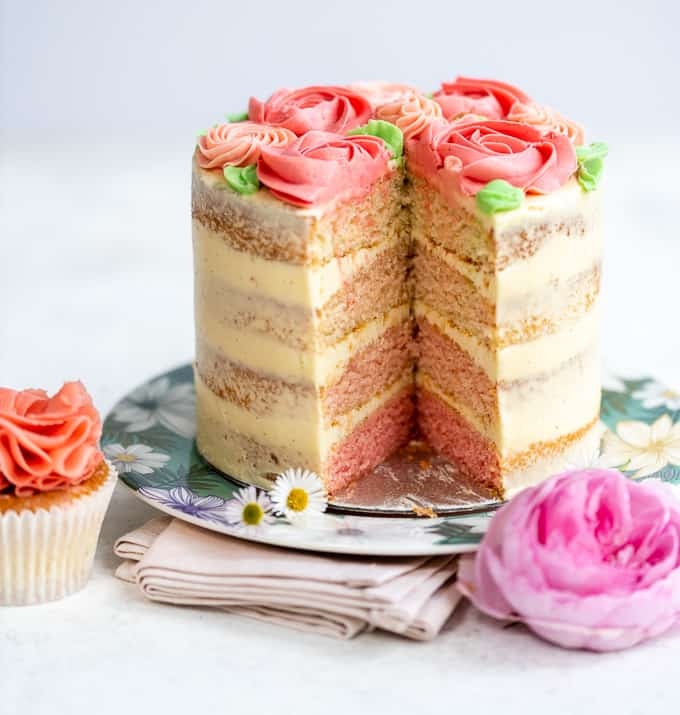 Pink ombre layer cake with slice taken out showing coloured layers
