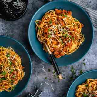 Table set with three bowls of Spaghetti Bolognese