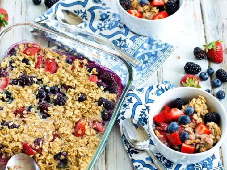 colorful glass dish of baked berry oatmeal on a blue and white country table
