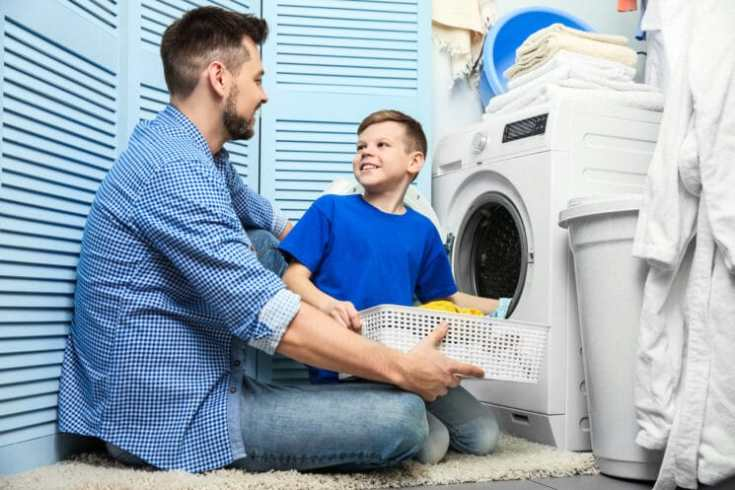 boy and his dad doing the laundry