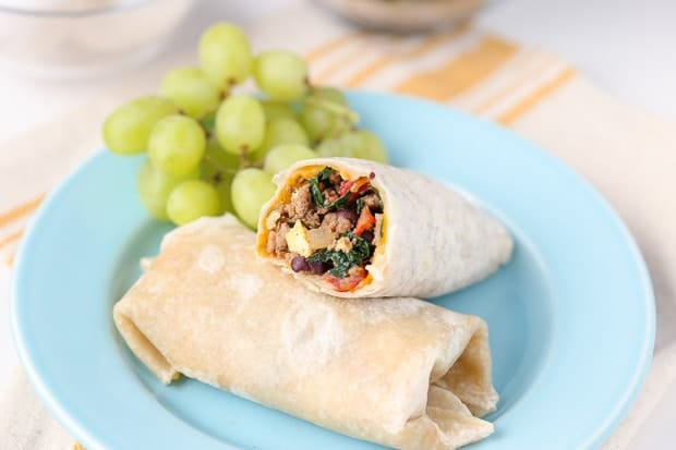 breakfast burrito on blue plate with grapes